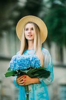 Jonge mooie vrouw in strohoed lacht naar binnen met hortensia op de zomerstraat