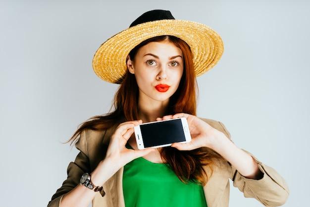 Jonge mooie vrouw in strohoed toont telefoon in verrassing