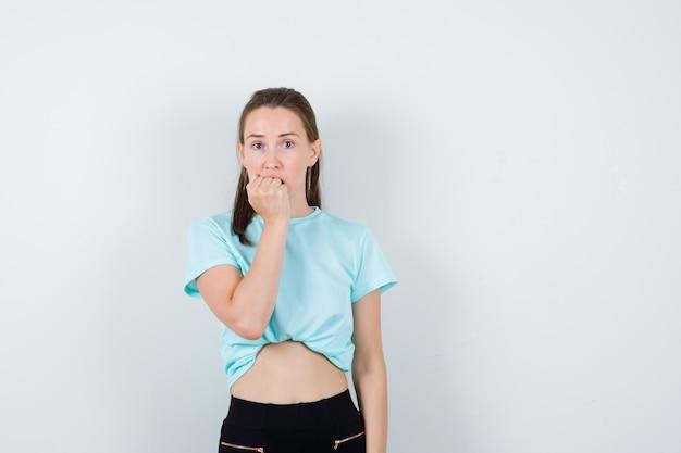 Jonge mooie vrouw in t-shirt, broek met hand op mond en doodsbang, vooraanzicht.
