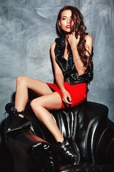 Jonge mooie vrouw in trendy zomer rode rok en jas.