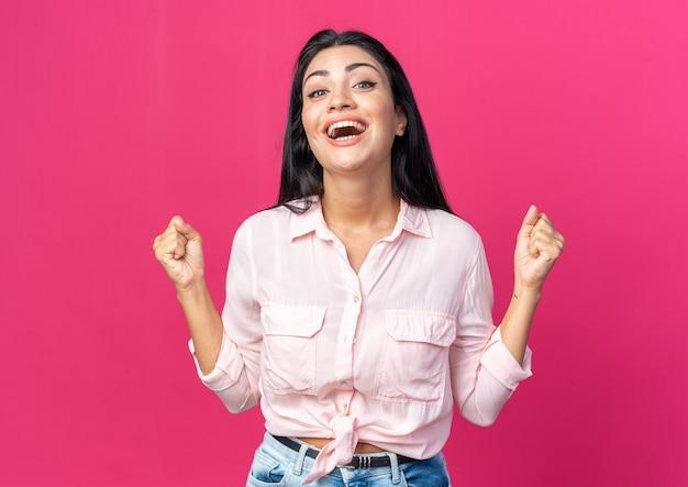 Jonge, mooie vrouw in vrijetijdskleding, blij en opgewonden, gebalde vuisten die over roze muur staan