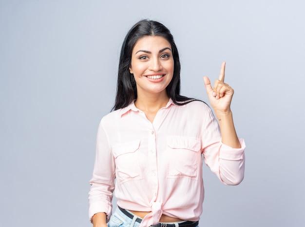 Jonge, mooie vrouw in vrijetijdskleding, blij en positief glimlachend, vrolijk tonend wijsvinger met een nieuw geweldig idee dat over een witte muur staat