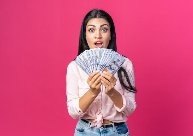 Jonge, mooie vrouw in vrijetijdskleding die contant geld vasthoudt en er verbaasd en verrast uitziet