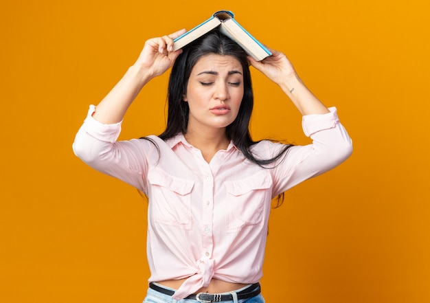 Jonge, mooie vrouw in vrijetijdskleding die een boek op haar hoofd houdt en van streek is terwijl ze op oranje staat