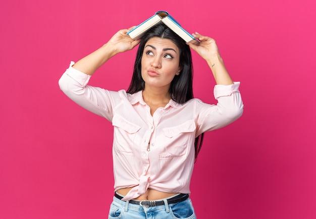 Jonge, mooie vrouw in vrijetijdskleding die een boek op het hoofd houdt en er verward en ontevreden uitziet terwijl ze op roze staat