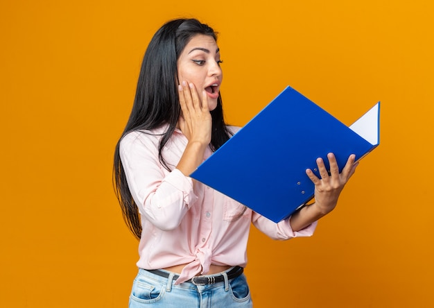 Jonge, mooie vrouw in vrijetijdskleding die een map vasthoudt en er blij en verrast naar kijkt terwijl ze op oranje staat