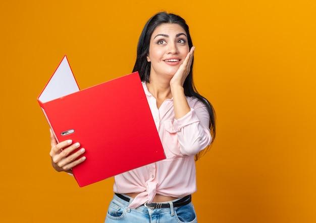 Jonge, mooie vrouw in vrijetijdskleding die een map vasthoudt en omhoog kijkt met een peinzende uitdrukking die positief denkt en vrolijk glimlacht terwijl ze op oranje staat