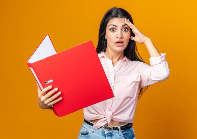 Jonge, mooie vrouw in vrijetijdskleding die een map verward en verrast houdt terwijl ze op oranje staat