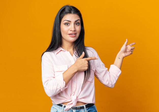 Jonge, mooie vrouw in vrijetijdskleding die er glimlachend zelfverzekerd blij en positief uitziet, wijzend met de wijsvinger naar de zijkant