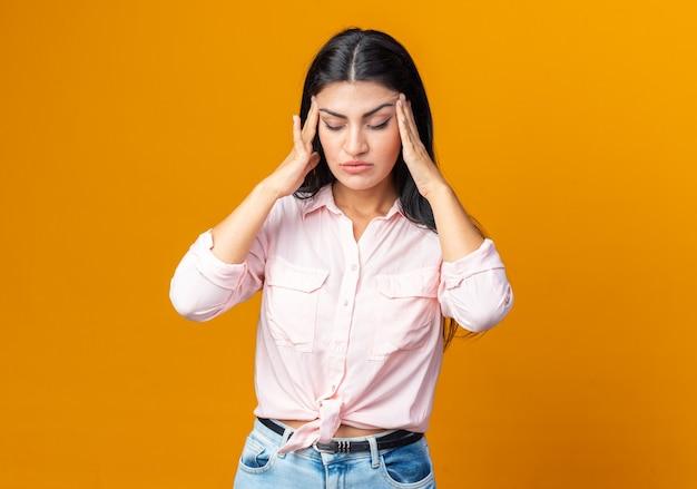 Jonge mooie vrouw in vrijetijdskleding die er onwel uitziet en haar slapen aanraakt die lijdt aan hoofdpijn die over een oranje muur staat