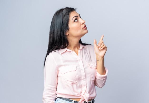 Jonge, mooie vrouw in vrijetijdskleding die geïntrigeerd opkijkt, wijzend met de wijsvinger die over een witte muur staat