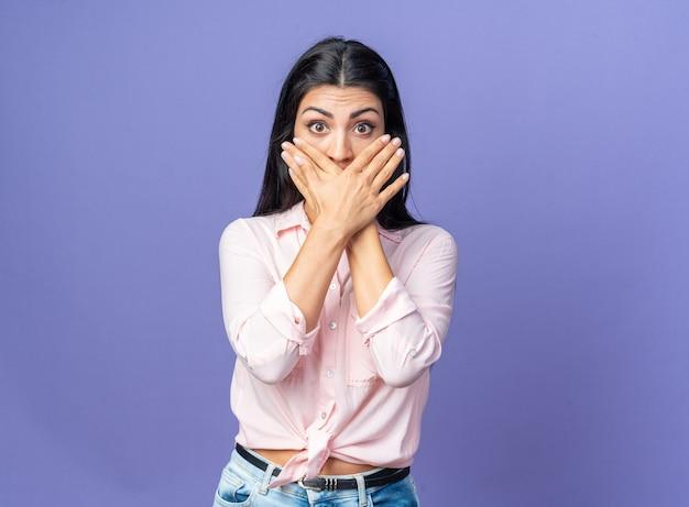 Jonge, mooie vrouw in vrijetijdskleding die geschokt is over de mond met handen die over de blauwe muur staan
