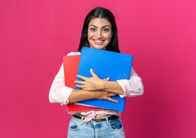 Jonge, mooie vrouw in vrijetijdskleding die kantoormappen vasthoudt en naar voren kijkt, blij en vrolijk glimlacht in grote lijnen over roze muur