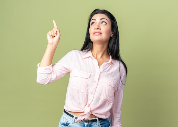 Jonge, mooie vrouw in vrijetijdskleding die met de wijsvinger omhoog kijkt naar iets dat lacht en over een groene muur staat