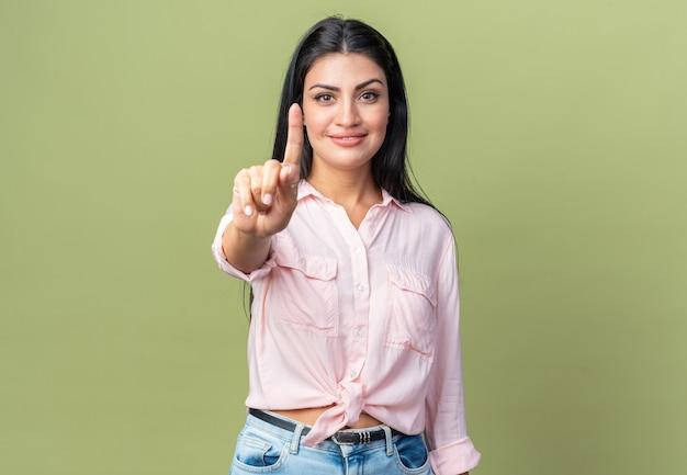 Jonge, mooie vrouw in vrijetijdskleding die naar de voorkant kijkt en zelfverzekerd glimlacht met wijsvinger die over een groene muur staat