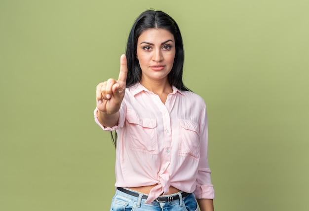 Jonge, mooie vrouw in vrijetijdskleding die naar voren kijkt met een zelfverzekerde uitdrukking die een waarschuwingsgebaar van de wijsvinger laat zien die over een groene muur staat
