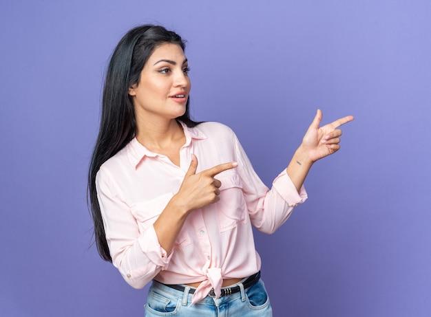 Jonge, mooie vrouw in vrijetijdskleding die opzij kijkt glimlachend zelfverzekerd wijzend met wijsvingers naar de zijkant die over de blauwe muur staat