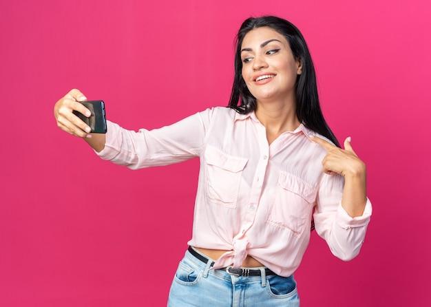 Jonge, mooie vrouw in vrijetijdskleding die selfie gelukkig en positief doet, wijzend naar zichzelf breed glimlachend