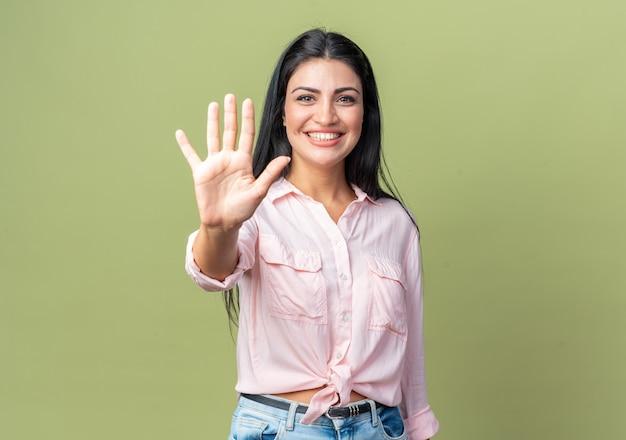 Jonge, mooie vrouw in vrijetijdskleding die vrolijk glimlacht en nummer vijf toont met open arm over groene muur