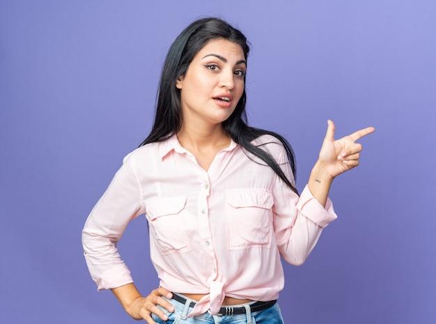 Jonge, mooie vrouw in vrijetijdskleding die zelfverzekerd glimlacht en met de wijsvinger naar de zijkant wijst die over de blauwe muur staat