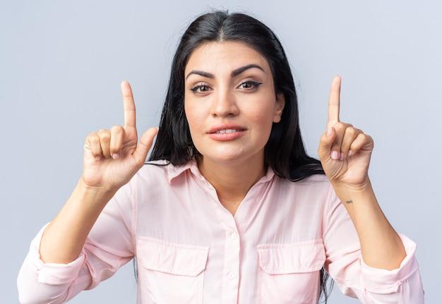 Jonge mooie vrouw in vrijetijdskleding glimlachend zelfverzekerd wijzend met wijsvingers omhoog staande over een witte muur