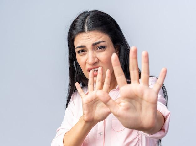 Jonge, mooie vrouw in vrijetijdskleding maakt zich zorgen om een stopgebaar te maken met handen die over een witte muur staan