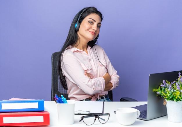 Jonge, mooie vrouw in vrijetijdskleding met een hoofdtelefoon die glimlacht, zelfverzekerd, gelukkig en positief aan de tafel zit met een laptop op blauw