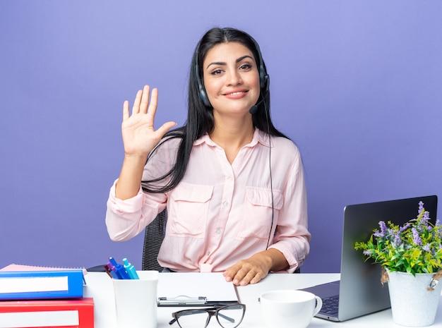 Jonge, mooie vrouw in vrijetijdskleding met een hoofdtelefoon met microfoon die lacht en nummer vijf laat zien die aan de tafel zit met een laptop over een blauwe muur die op kantoor werkt