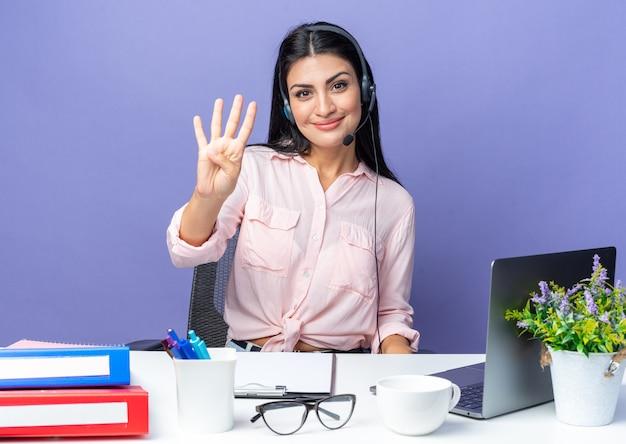 Jonge, mooie vrouw in vrijetijdskleding met een koptelefoon met nummer vier glimlachend zelfverzekerd zittend aan de tafel met laptop op blauw