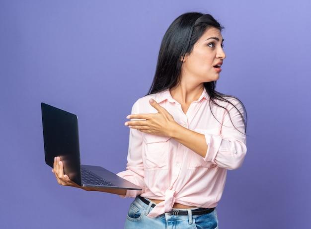 Jonge, mooie vrouw in vrijetijdskleding met een laptop die met de arm naar het scherm wijst en verward opzij kijkt terwijl ze over een blauwe muur staat