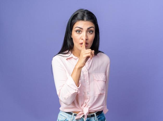 Jonge, mooie vrouw in vrijetijdskleding met een serieus gezicht die een stiltegebaar maakt met de vinger op de lippen die over de blauwe muur staat