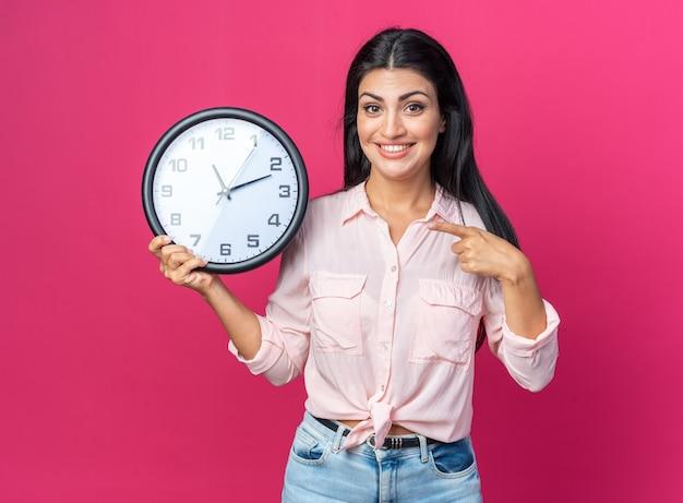 Jonge, mooie vrouw in vrijetijdskleding met een wandklok die met de wijsvinger erop wijst en vrolijk glimlacht terwijl ze op roze staat