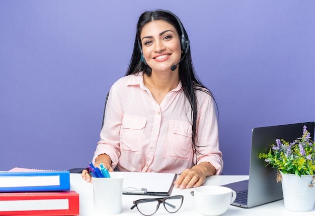 Jonge mooie vrouw in vrijetijdskleding met koptelefoon en microfoon die glimlachend vrolijk aan tafel zit met laptop over blauwe achtergrond die op kantoor werkt