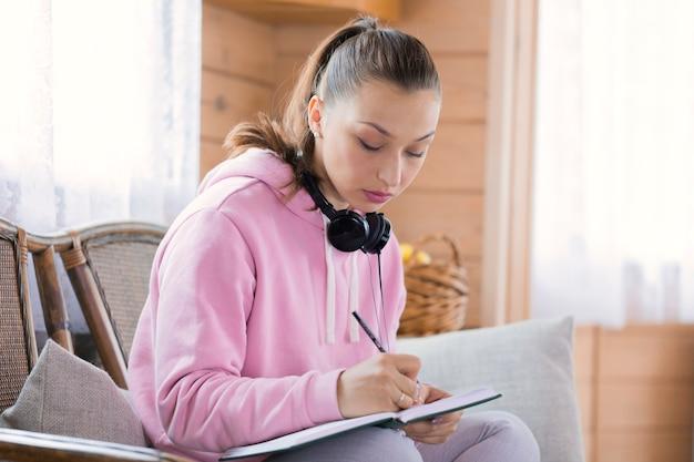 Jonge mooie vrouw in vrijetijdskleding thuis studeren, notities schrijven in notitieblok