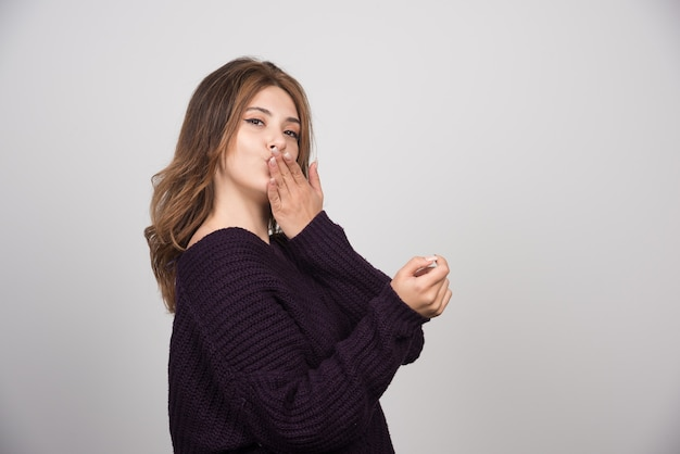 Jonge mooie vrouw in warme gebreide trui die een luchtkus blaast.