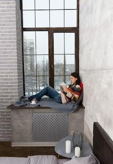 Jonge mooie vrouw in warme gebreide trui liggend op de vensterbank met kussens en deken en het lezen van een boek in de slaapkamer