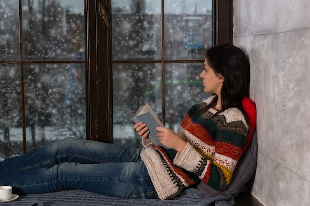 Jonge mooie vrouw in warme gebreide trui met een boek, liggend op de vensterbank met kussens en deken en uit het raam kijkend terwijl het sneeuwt