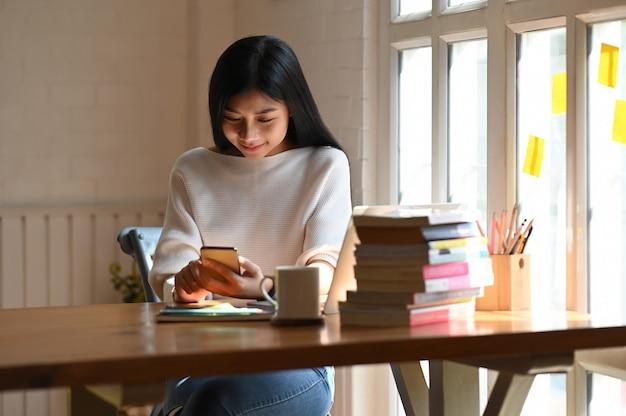 Jonge mooie vrouw in wit katoenen overhemd die / smartphone in haar handen houden gebruiken terwijl samen het zitten met laptop, koffiekop, potloodhouder en stapel boeken die op houten lijst zetten.