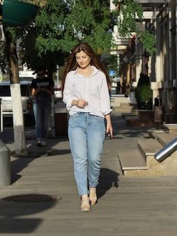 Jonge mooie vrouw in witte blouse en spijkerbroek loopt langzaam door de straat