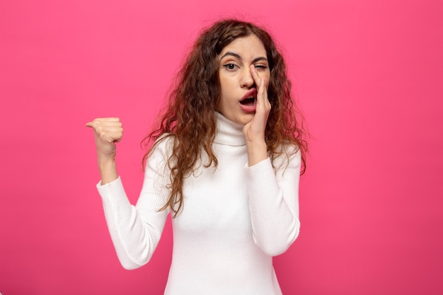 Jonge mooie vrouw in witte coltrui die een geheime hand op de mond vertelt en met de duim naar de zijkant wijst die op roze staat