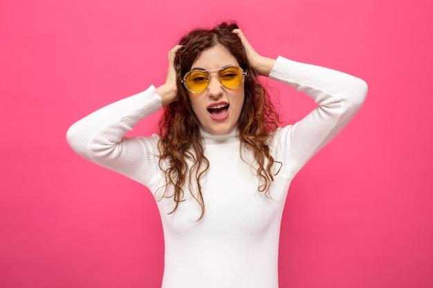 Jonge mooie vrouw in witte coltrui met een gele bril die aan haar haar trekt en gefrustreerd staat op roze