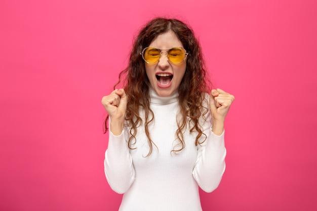 Jonge, mooie vrouw in witte coltrui met een gele bril die schreeuwt en schreeuwt, gefrustreerd, gekke, gebalde vuisten die op roze staan