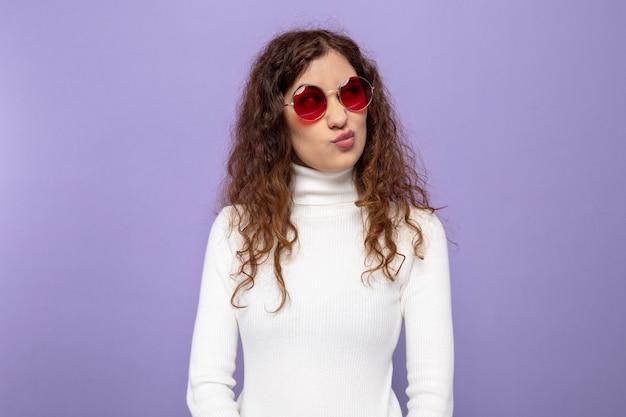 Jonge, mooie vrouw in witte coltrui met een rode bril die opzij kijkt met een negatieve uitdrukking die een wrange mond maakt