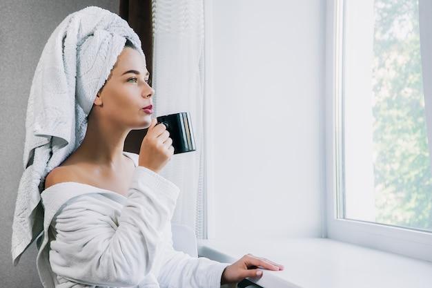 Jonge mooie vrouw in witte handdoek en kleed het drinken koffie dichtbij het venster thuis