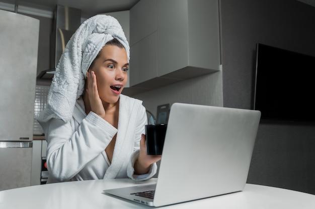 Jonge mooie vrouw in witte handdoek en kleed koffie drinken en kijken op laptop scherm aan de tafel