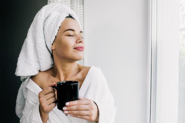 Jonge mooie vrouw in witte handdoek en robe koffie drinken en genieten van in de buurt van het raam thuis