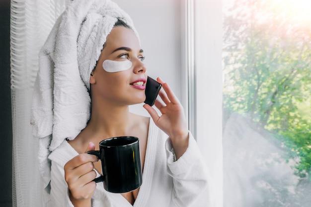 Jonge mooie vrouw in witte handdoek en robe koffie drinken en praten aan de telefoon bij het raam thuis
