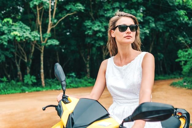 Jonge mooie vrouw in witte jurk met scooter