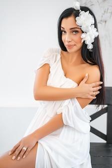 Jonge mooie vrouw in witte kledingszitting op stoel.