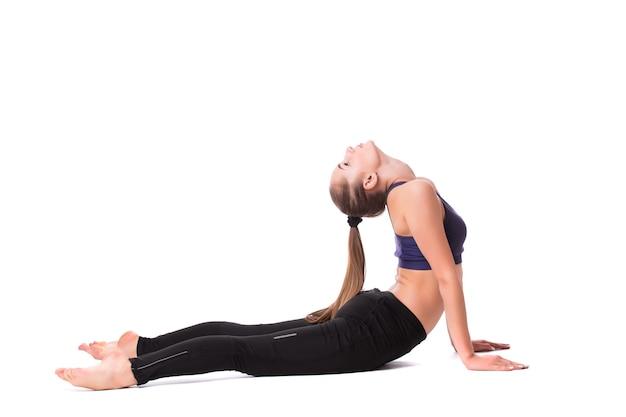 Jonge mooie vrouw in witte sportkleding maakt yoga-oefeningen op een witte achtergrond